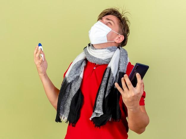 Młody przystojny blondyn chory ubrany w maskę i szalik trzymając termometr i telefon komórkowy patrząc na białym tle na oliwkowym tle