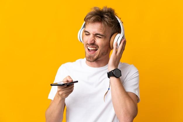 Młody przystojny blondyn na białym tle na żółty słuchanie muzyki z telefonu komórkowego i śpiewu