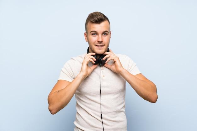 Młody przystojny blondynka mężczyzna nad odosobnioną błękit ścianą słucha muzyka z hełmofonami
