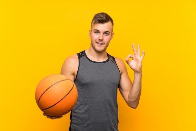 Młody przystojny blondynka mężczyzna trzyma koszykową piłkę nad odosobnioną kolor żółty ścianą pokazuje ok znaka z palcami