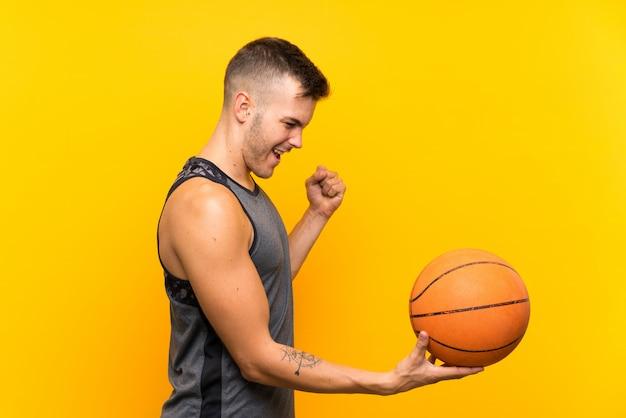 Młody przystojny blondynka mężczyzna trzyma koszykową piłkę nad odosobnioną kolor żółty ścianą świętuje zwycięstwo