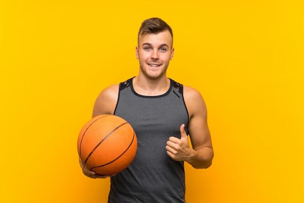 Młody przystojny blondynka mężczyzna trzyma piłkę do kosza na pojedyncze żółte ściany z kciuki do góry, ponieważ stało się coś dobrego