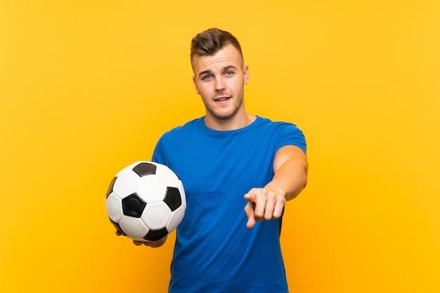 Młody przystojny blondynka mężczyzna trzyma piłkę nożną nad odosobnionymi żółtymi ściennymi punktami dotyka ciebie z ufnym wyrażeniem