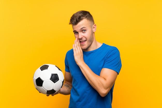 Młody przystojny blondynka mężczyzna trzyma piłkę nożną szepcząc coś