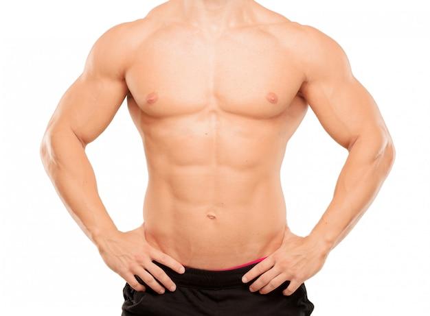 Młody przystojny bodybuilder mężczyzna pozuje z mięśniowym pojawieniem