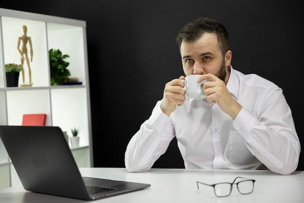 Młody przystojny brodaty biznesmen marzy w białej koszula cieszy się filiżankę cappuccino, męski freelancer siedzi przy biurku przed laptopem w domowym biurze. niezależny, zdalna praca, koncepcja samozatrudnienia