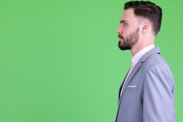 Młody przystojny brodaty biznesmen w garniturze przeciwko klucz chrominancji z zieloną ścianą