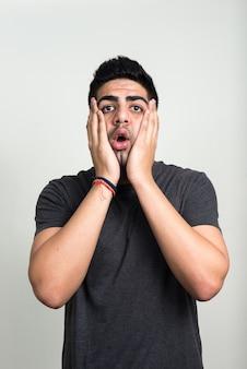 Młody przystojny brodaty mężczyzna indyjski przeciw białej ścianie