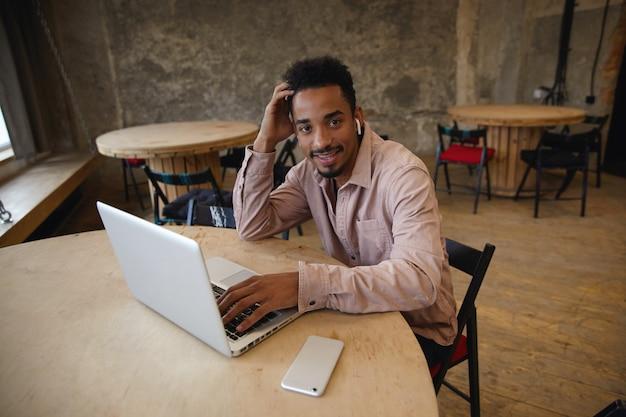 Młody przystojny brodaty mężczyzna o ciemnej skórze siedzi przy stole z laptopem i smartfonem, pozytywnie patrzy na kamerę i trzyma głowę z uniesioną ręką, pozuje nad wnętrzem kawiarni miejskiej