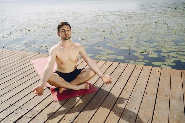 Młody przystojny brodaty mężczyzna siedzi na drewnianym molo w letni dzień. medytując i relaksując się.