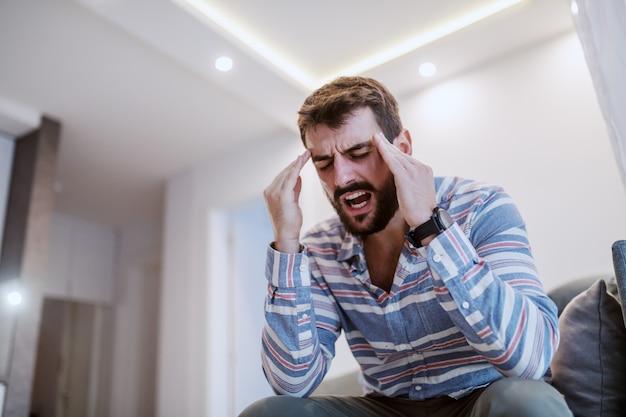 Młody przystojny brodaty mężczyzna siedzi na kanapie w salonie, trzymając głowę i mając ból głowy.
