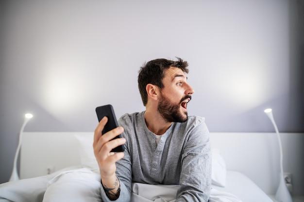 Młody przystojny brodaty mężczyzna siedzi na łóżku w sypialni i trzyma inteligentny telefon