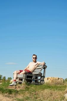 Młody przystojny brodaty mężczyzna w okularach przeciwsłonecznych, opalając się, siedząc na drewnianej ławce na tle jasnego nieba