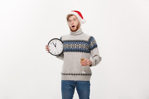 Młody przystojny brodaty mężczyzna w sweter z białym zegarem i szampanem na białym tle
