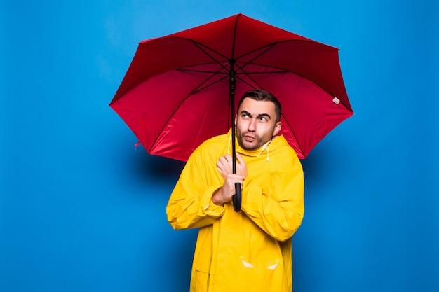 Młody przystojny brodaty mężczyzna w żółtym płaszczu przeciwdeszczowym z czerwoną osłoną parasola przed deszczem, na białym tle na niebieskim tle