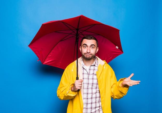 Młody przystojny brodaty mężczyzna w żółtym płaszczu z czerwonym parasolem na białym tle nad niebieskim tle