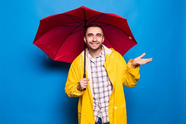 Młody przystojny brodaty mężczyzna w żółtym płaszczu z czerwonym parasolem próbuje sprawdzić, czy pada na białym tle na niebieskim tle