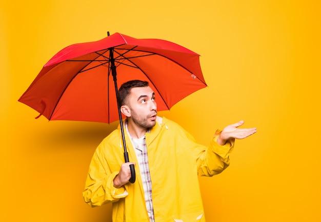 Młody przystojny brodaty mężczyzna w żółtym płaszczu z czerwonym parasolem próbuje sprawdzić, czy pada na białym tle na pomarańczowym tle