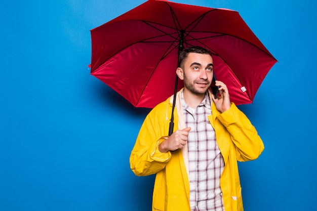 Młody przystojny brodaty mężczyzna w żółtym płaszczu z czerwonym parasolem rozmawia przez telefon komórkowy na białym tle na niebieskim tle