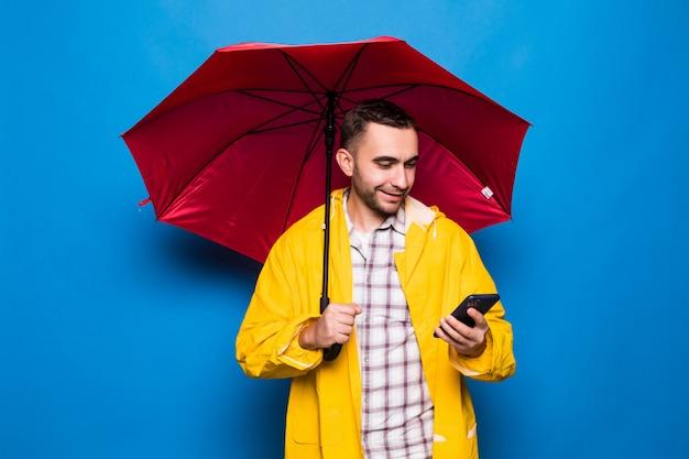 Młody przystojny brodaty mężczyzna w żółtym płaszczu z czerwonym parasolem używać telefonu komórkowego na białym tle na niebieskim tle