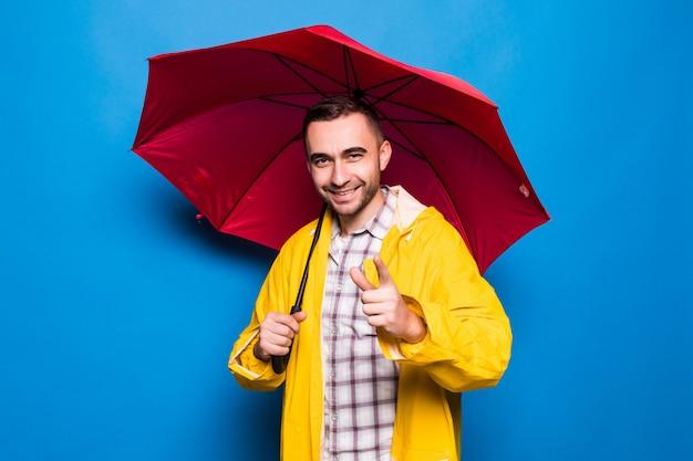 Młody przystojny brodaty mężczyzna w żółtym płaszczu z czerwonym parasolem wskazał na ciebie na białym tle na niebieskim tle