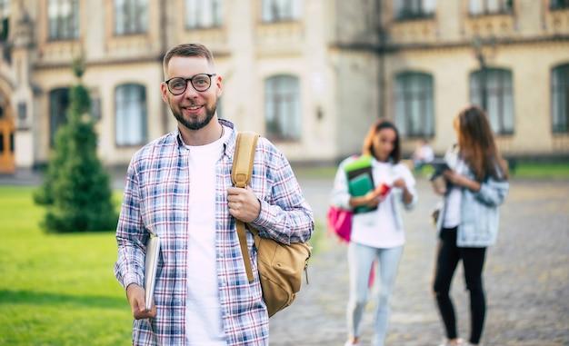 Młody przystojny brodaty student facet w ubranie z plecakiem i książkami w rękach chodzi i pozuje na budynkach uniwersytetu