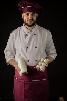 Młody przystojny brodaty szefa kuchni mężczyzna w mundurze trzyma butelkę mleka i jaj