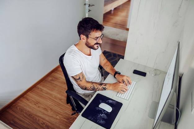 Młody przystojny brodaty uśmiechnięty freelancer siedzi w swoim domowym biurze i pisze ważne rzeczy o nowym projekcie.