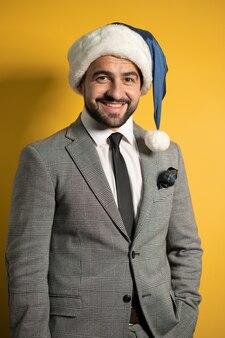 Młody przystojny brodaty uśmiechnięty mężczyzna santa na sobie niebieski kapelusz świętego mikołaja i garnitur