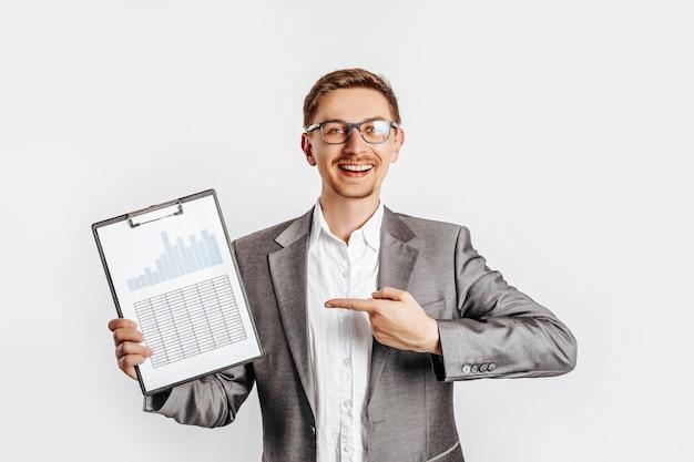 Młody przystojny brunet mężczyzna w okularach w garniturze uśmiecha się i wskazuje na biznes z dokumentów i wykresów na na białym tle