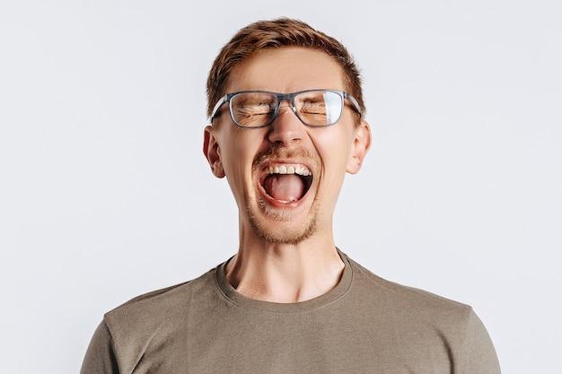 Młody przystojny brunet w okularach jest nieszczęśliwy krzyki i na białym tle