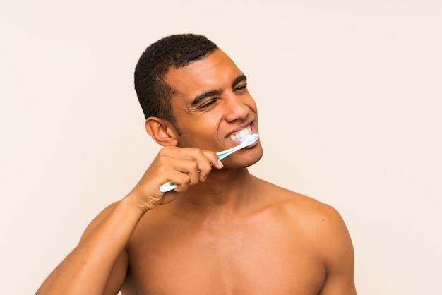 Młody przystojny brunetka mężczyzna szczotkuje zęby