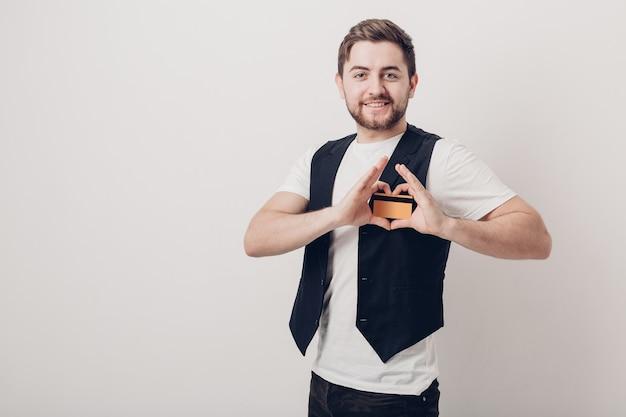 Młody przystojny brunetka mężczyzna z brodą w białej koszuli i czarnej kamizelce, trzymając plastikową kartę kredytową i uśmiechając się. miękkie światło