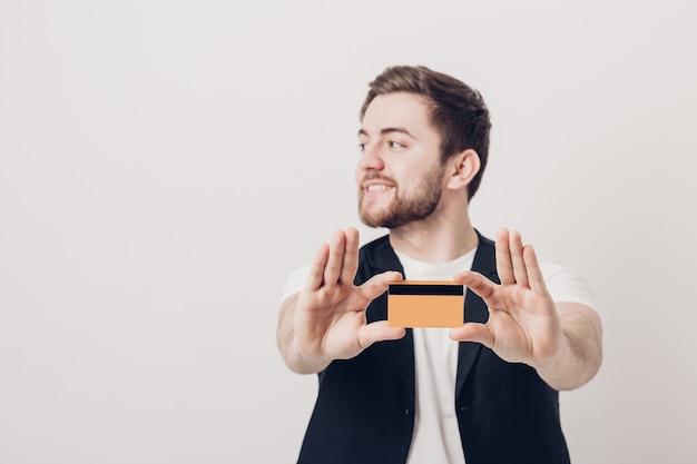 Młody przystojny brunetka mężczyzna z brodą w białej koszuli i czarnej kamizelce, trzymając plastikową kartę kredytową i uśmiechając się. skoncentruj się na karcie. miękkie światło