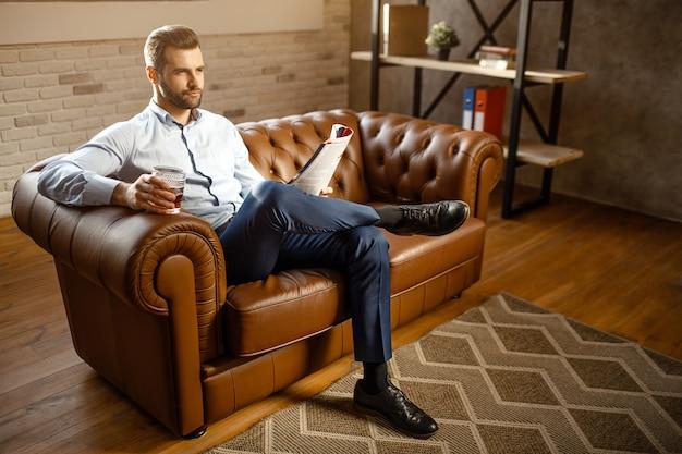 Młody przystojny buisnessman siedzi na kanapie i pije whisky w swoim własnym biurze. patrzy prosto z pewnością. facet trzyma dziennik. atrakcyjny mały uśmiech.