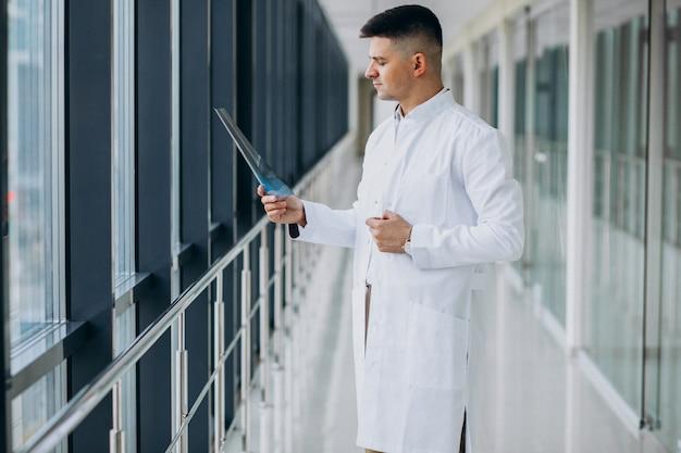 Młody przystojny chirurg patrzeje promieniowanie rentgenowskie
