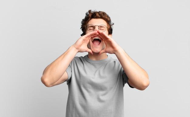 Młody przystojny chłopak czuje się szczęśliwy, podekscytowany i pozytywnie nastawiony, wydaje wielki okrzyk z rękami przy ustach, wołając