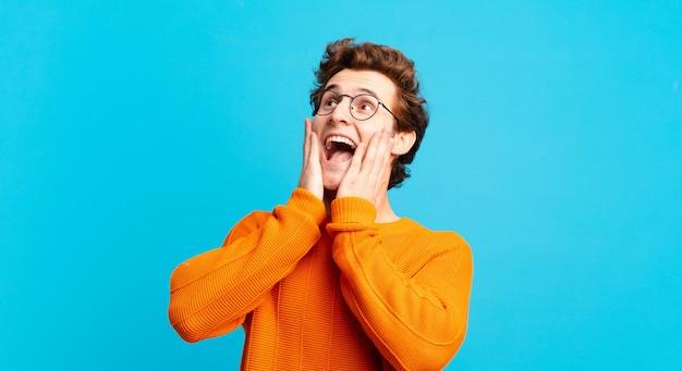 Młody przystojny chłopak czuje się szczęśliwy, podekscytowany i zaskoczony, patrząc w bok z obiema rękami na twarzy