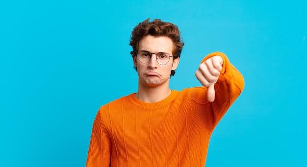 Młody przystojny chłopak czuje się zły, zły, zirytowany, rozczarowany lub niezadowolony, pokazując kciuk w dół z poważnym spojrzeniem