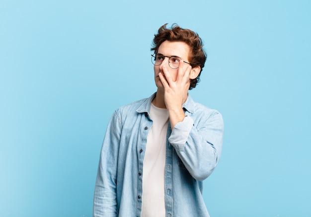 Młody przystojny chłopak czuje się znudzony, sfrustrowany i senny po męczącym, nudnym i żmudnym zadaniu, trzymając twarz dłonią