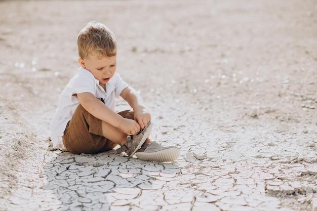Młody przystojny chłopak siedzi na ziemi