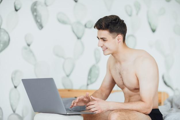 Młody przystojny chłopak siedzi w łóżku i pracuje rano na swoim laptopie
