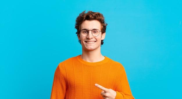 Młody przystojny chłopak uśmiecha się radośnie, czuje się szczęśliwy i wskazuje na bok i do góry, pokazując obiekt w przestrzeni kopii