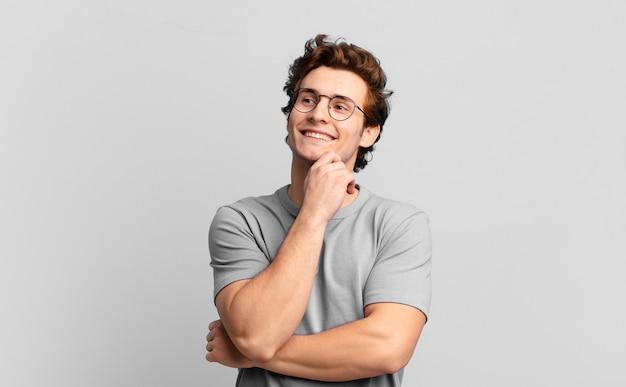 Młody przystojny chłopak uśmiecha się radośnie i marzy lub wątpi, patrząc w bok