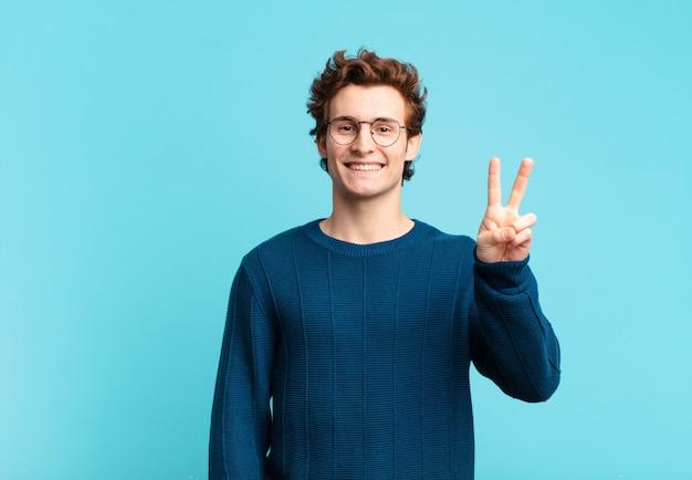 Młody przystojny chłopak uśmiechający się i patrzący przyjaźnie, pokazujący numer dwa lub drugi z ręką do przodu, odliczający w dół