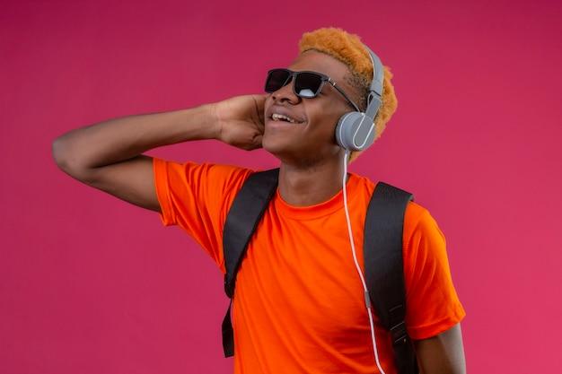Młody przystojny chłopak z plecakiem i słuchawkami, ciesząc się ulubioną muzyką szczęśliwy i pozytywny uśmiechnięty stojący nad różową ścianą