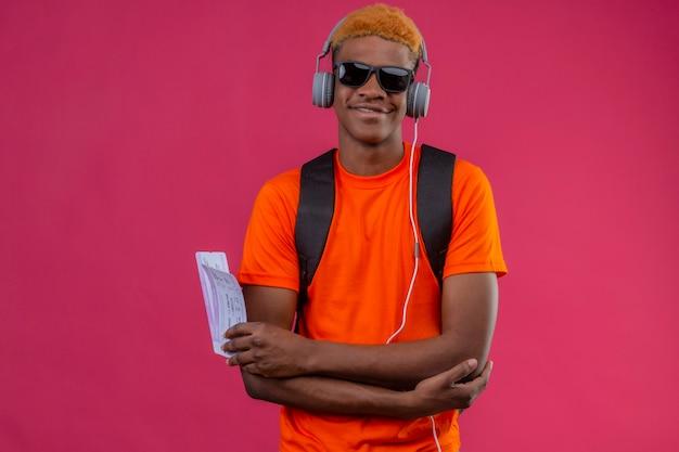 Młody przystojny chłopak z plecakiem i słuchawkami, trzymając bilety lotnicze, ciesząc się ulubioną muzyką