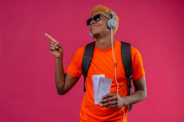 Młody przystojny chłopak z plecakiem i słuchawkami, trzymając bilety lotnicze, wskazując palcem na bok, ciesząc się ulubioną muzyką