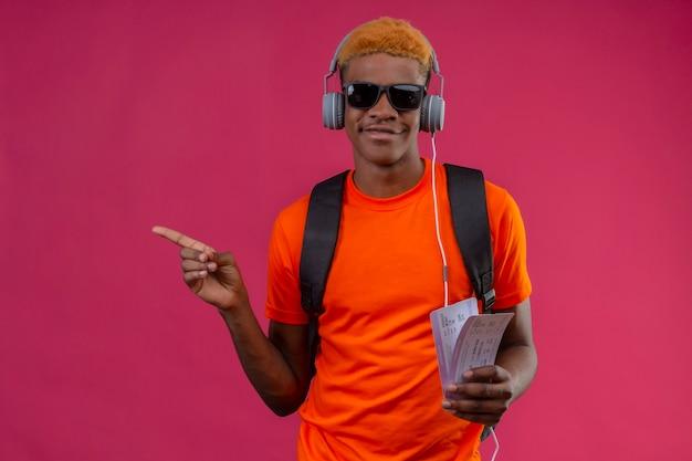 Młody przystojny chłopak z plecakiem i słuchawkami, trzymając bilety lotnicze wskazując palcem na bok szczęśliwy i pozytywny uśmiechnięty stojący nad różową ścianą