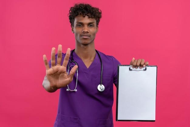 Młody przystojny ciemnoskóry lekarz z kręconymi włosami ubrany w fioletowy mundur ze stetoskopem pokazujący schowek z pustą kartką papieru